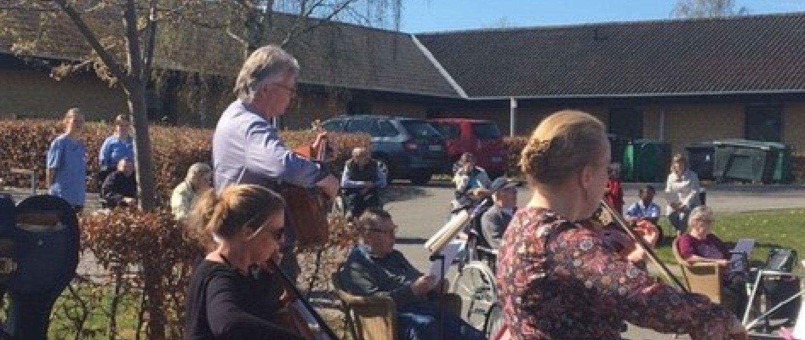 Musikere spiller udendørs ved plejecenter